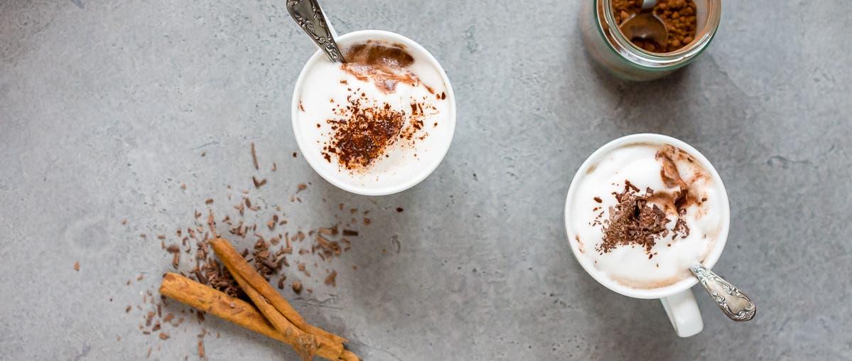 Bild von oben von zwei Tassen gefüllt mit heißer Schokolade, Milchschaum und geraspelter Schokolade. Daneben zwei Zimtstangen.