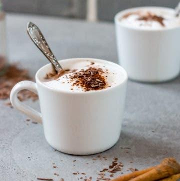 Weiße Tasse mit Milchschaum, einem Teelöffel und geraspelter Schokolade.