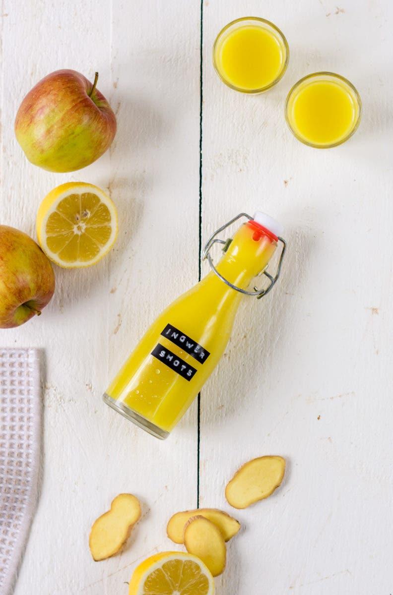 Topshot Ingwer Shot Bügelflasche, zwei Ingwer Shot Gläser, Apfel, Zitrone und Ingwer.