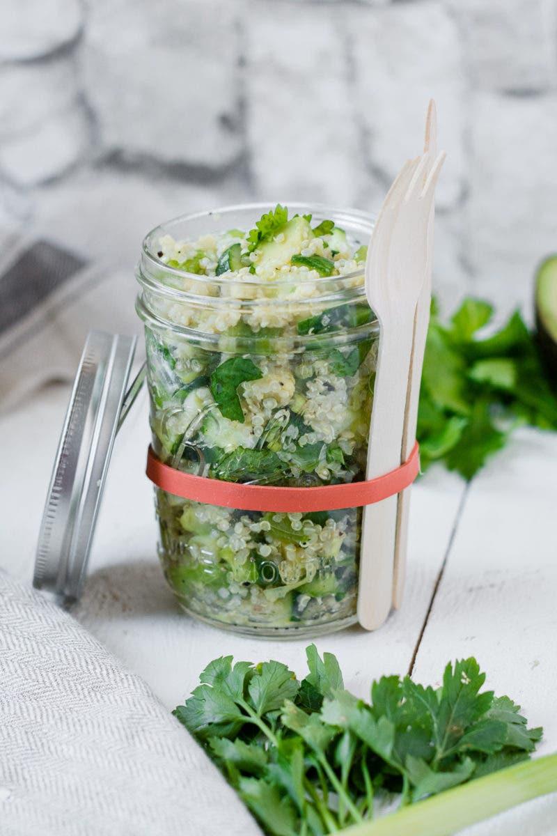 Quinoasalat mit frischen Kräutern in einem Glas mit zwei Gabeln zum Mitnehmen.