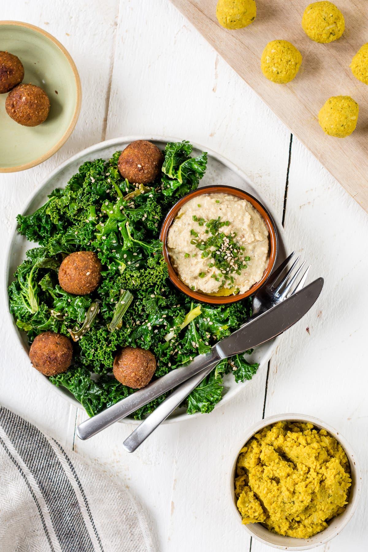 Topshot Curry-Falafeln mit gebratenem Grünkohl und Hummus, daneben Falafel Bällchen vor dem Backen