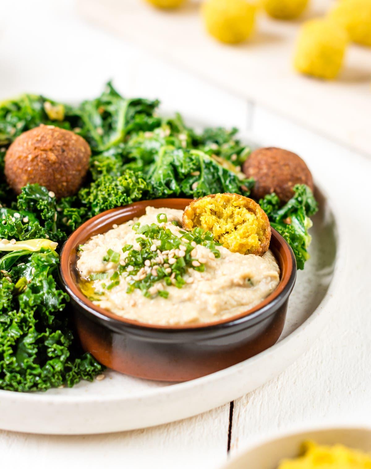 Schnelle Curry-Falafeln mit gebratenem Grünkohl und Hummus, im Hintergrund Falafel Bällchen vor dem Backen