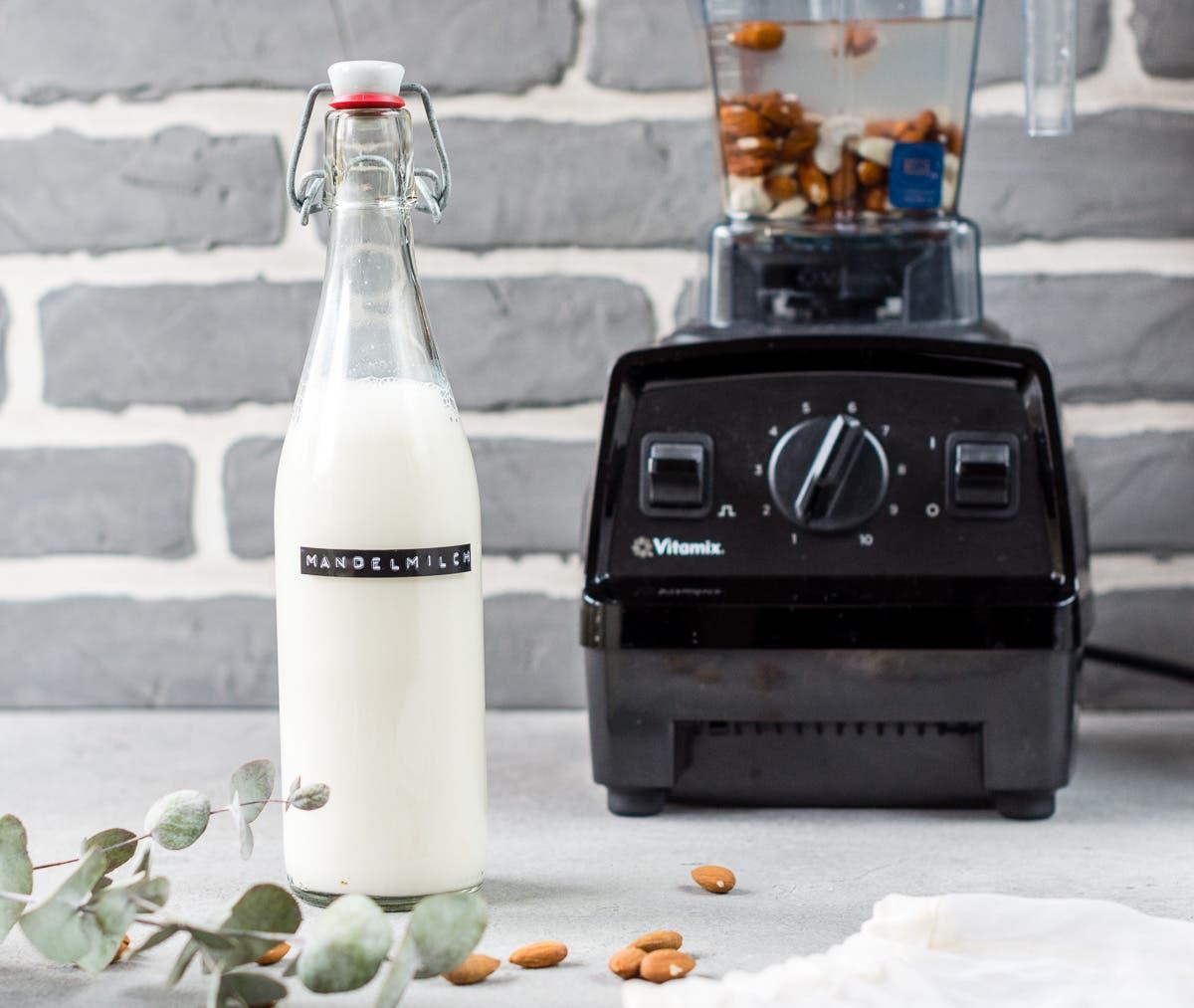 Flasche mit Mandelmilch steht vor einem schwarzen Mixer.