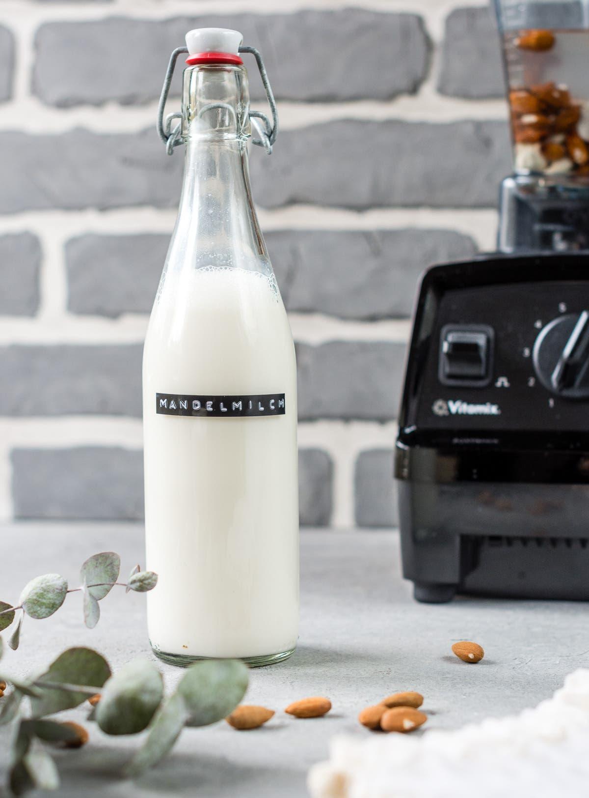 Selbstgemachte Mandelmilch in Bügelflasche vor Mixer
