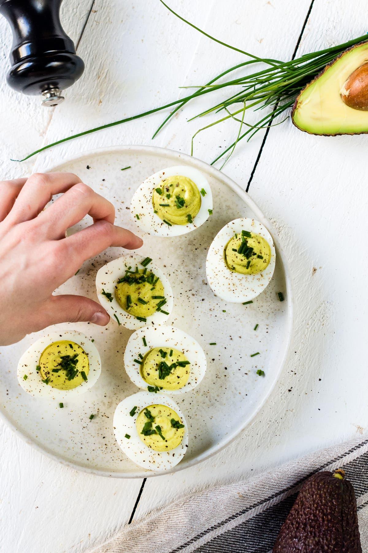 Person greift nach mit Avocado gefüllten Eiern mit Schnittlauch auf einem Teller.