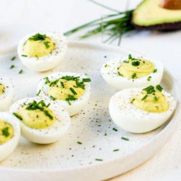 Mit Avocado gefüllte Eier mit Schnittlauch auf einem Teller.