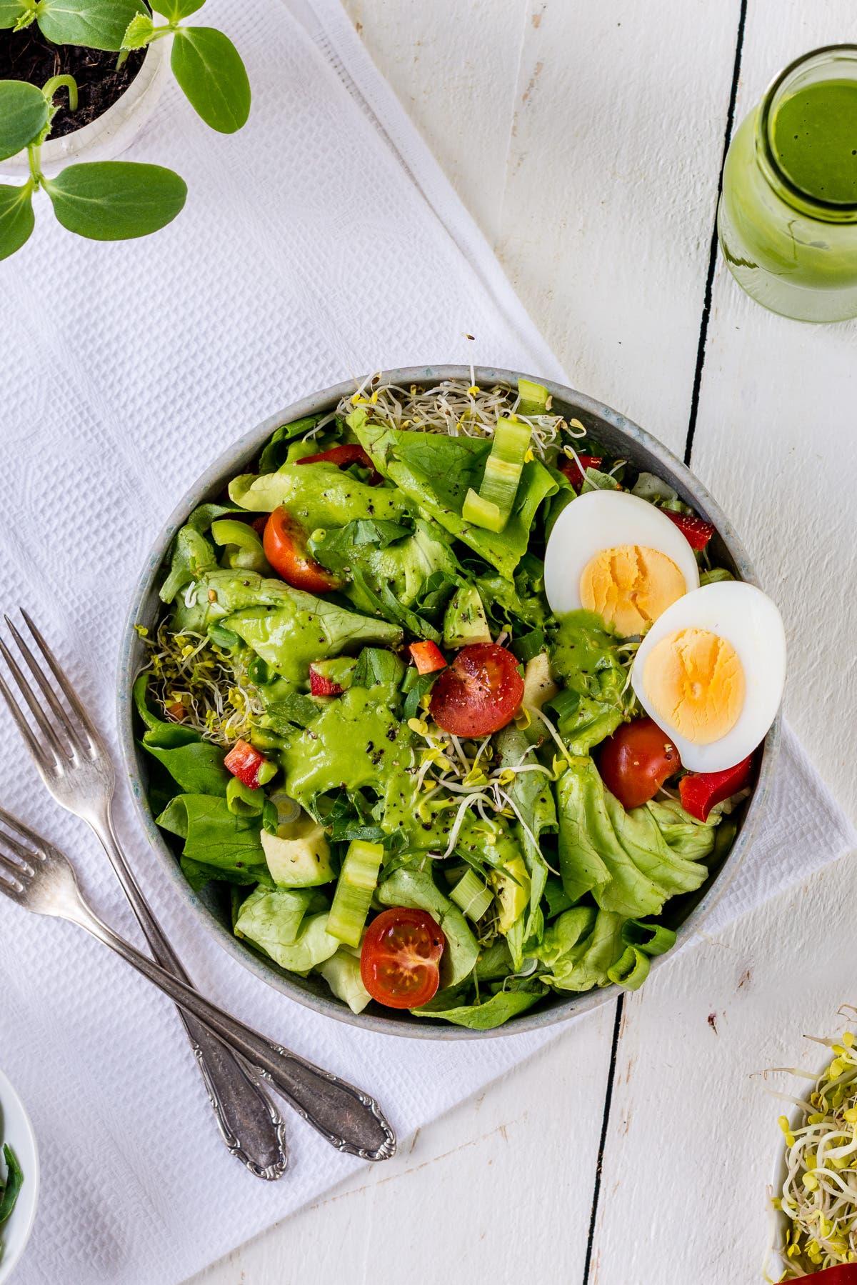 Topshot von Teller mit grünem Salat, Tomaten, Sprossen und zwei Eierhälften