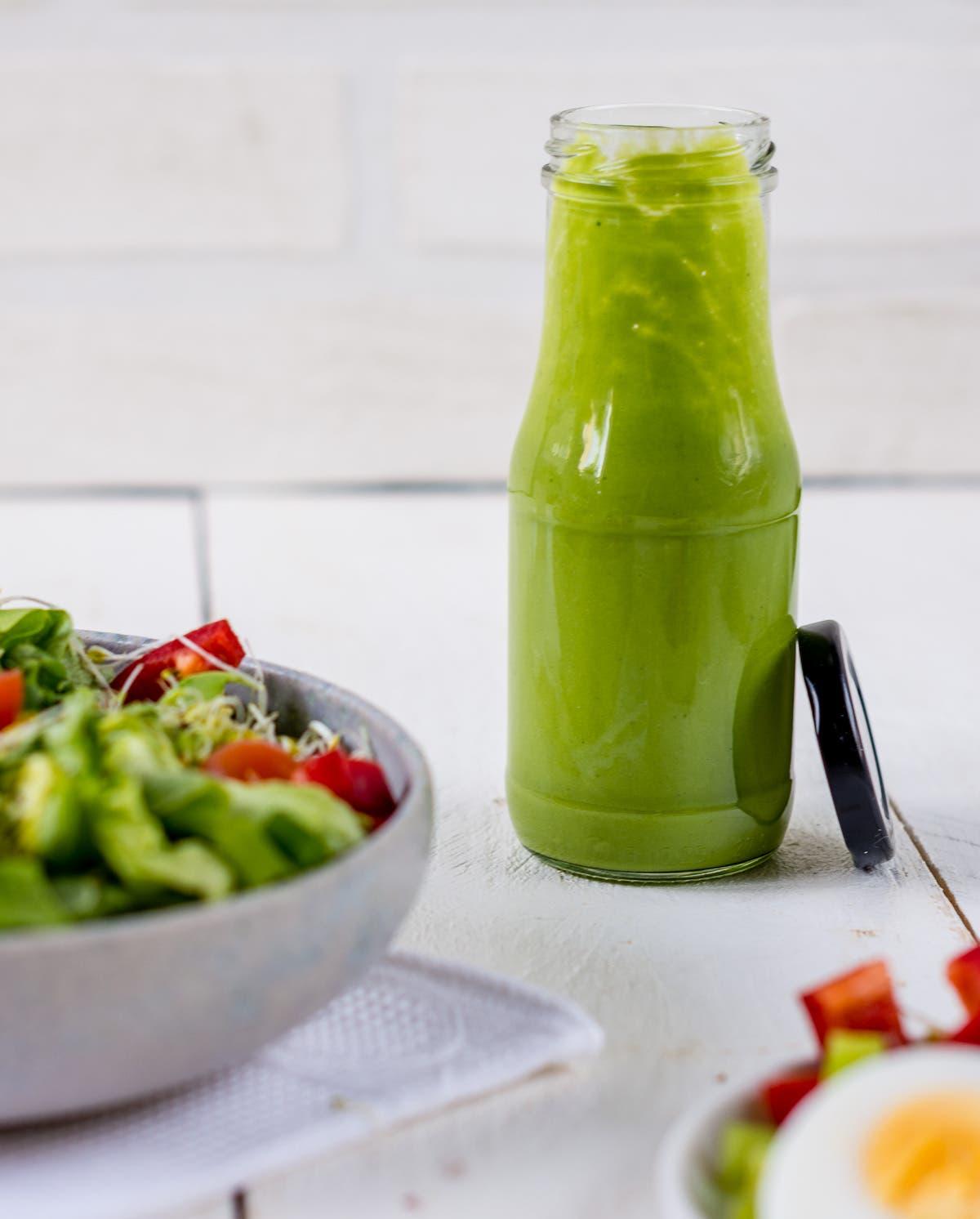 Offene Flasche mit grünem Salatdressing.
