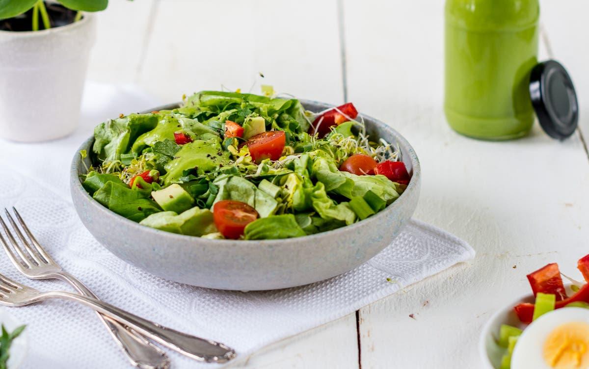 Schüssel mit grünem Salat, Tomaten und Sprossen.