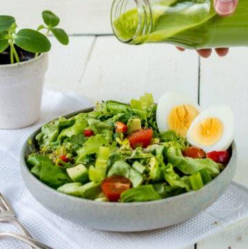Teller mit grünem Salat, Tomaten und Eiern. Eine Hand hält eine Flasche mit grünem Salatdressing.