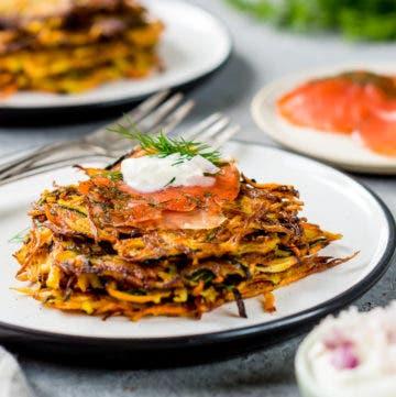 Teller gefüllt mit Zucchini Möhren Puffern und frischem Lachs und Kräuterquark.