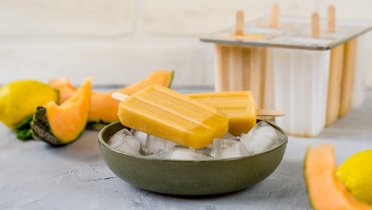 Eine Schüssel mit Eiswürfel auf denen zwei gelbe Eis am Stiel liegen. Im Hintergrund liegt eine Zitrone und Melonenstücke.