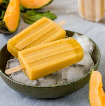 Zwei gelbe Eis am Stiel auf Eiswürfeln in einer Schüssel. Im Hintergrund liegen aufgeschnittene Melonenstücke.