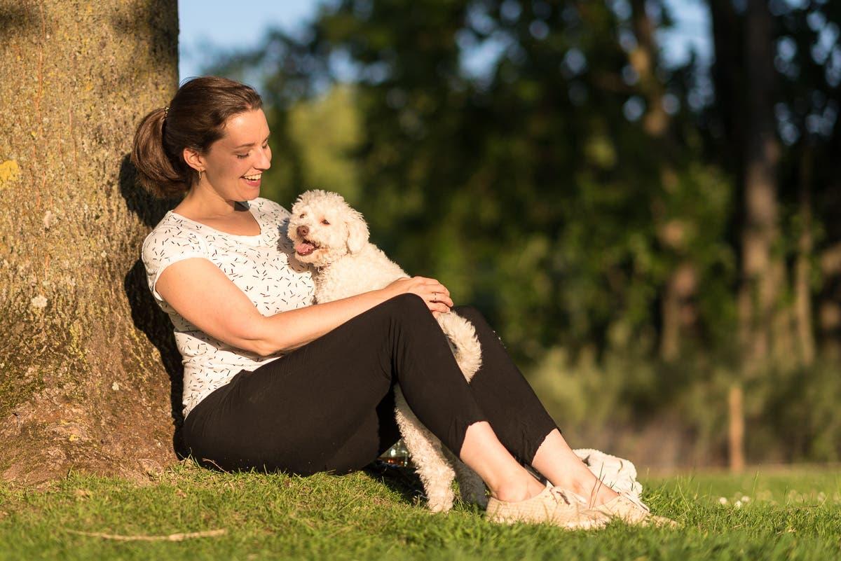 Frau sitzt auf einer Wiese und lehnt sich an einen Baum. Dabei lächelt sie ihren Pudel an.