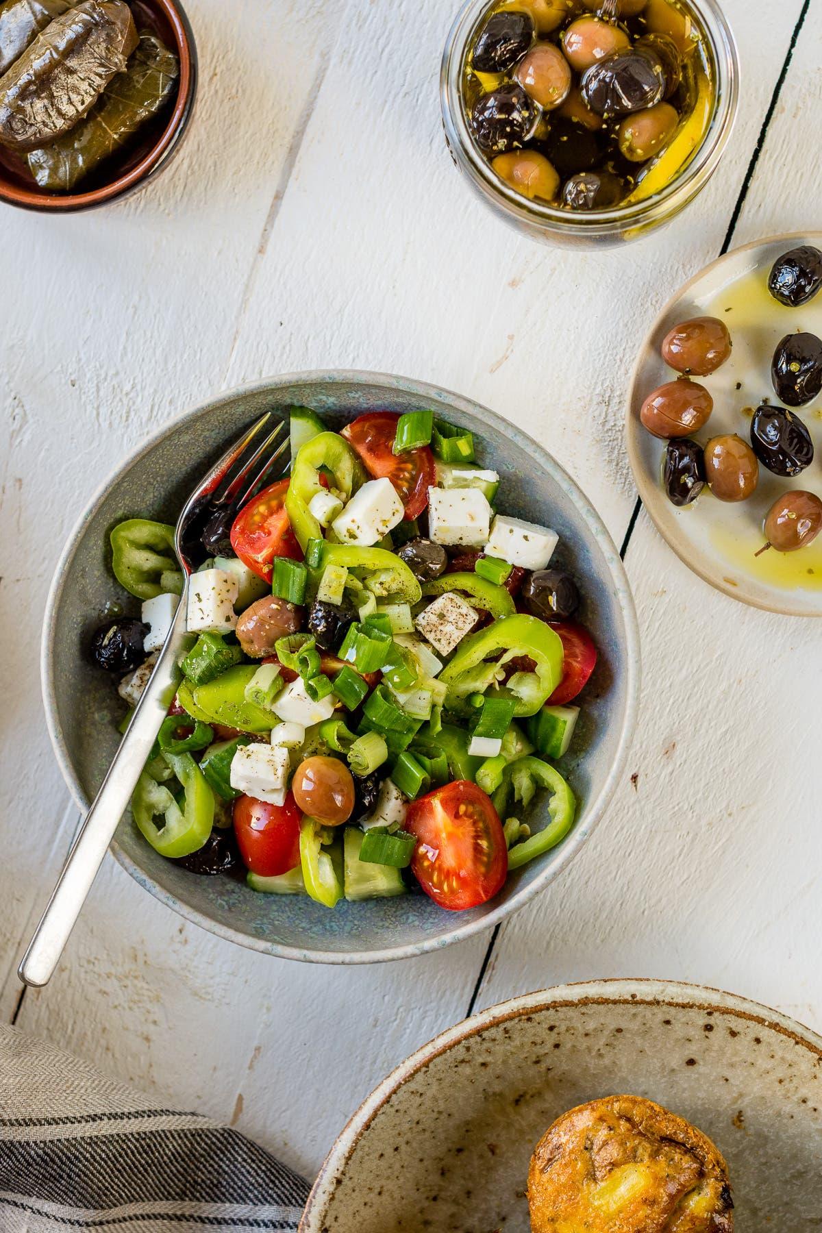 Bild von oben mit einer Schüssel Salat und ein Teller und ein Glas mit eingelegten Oliven auf weißem Untergrund.