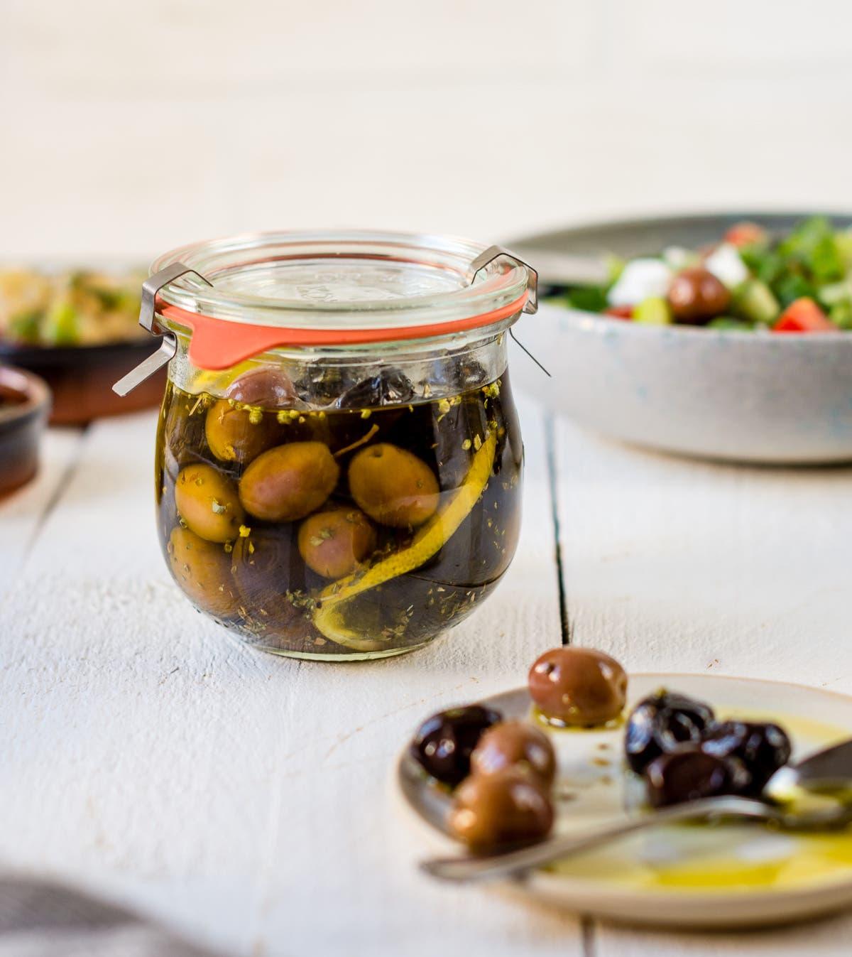 Glas mit eingelegten Oliven und ein Teller mit einem Teelöffel und Oliven auf weißem Untergrund.