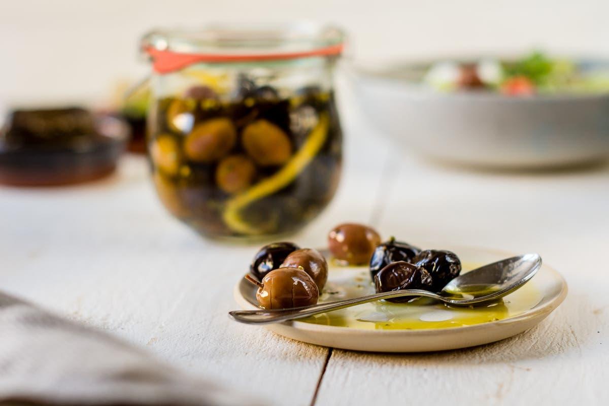 Glas und ein kleiner Teller mit eingelegten Oliven.