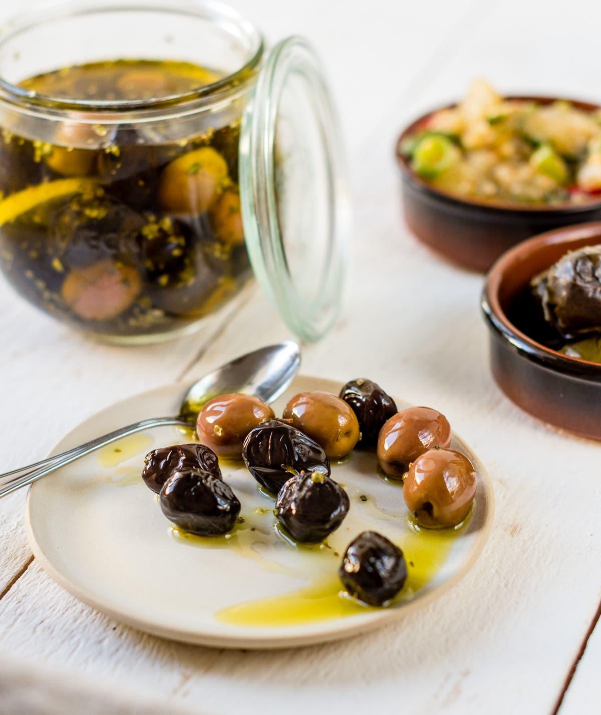 Glas und kleiner Teller mit eingelegten schwarzen und hellen Oliven auf weißem Untergrund.