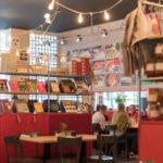 Restaurant mit einem Bücherregal und einer Lichterkette an der Decke.