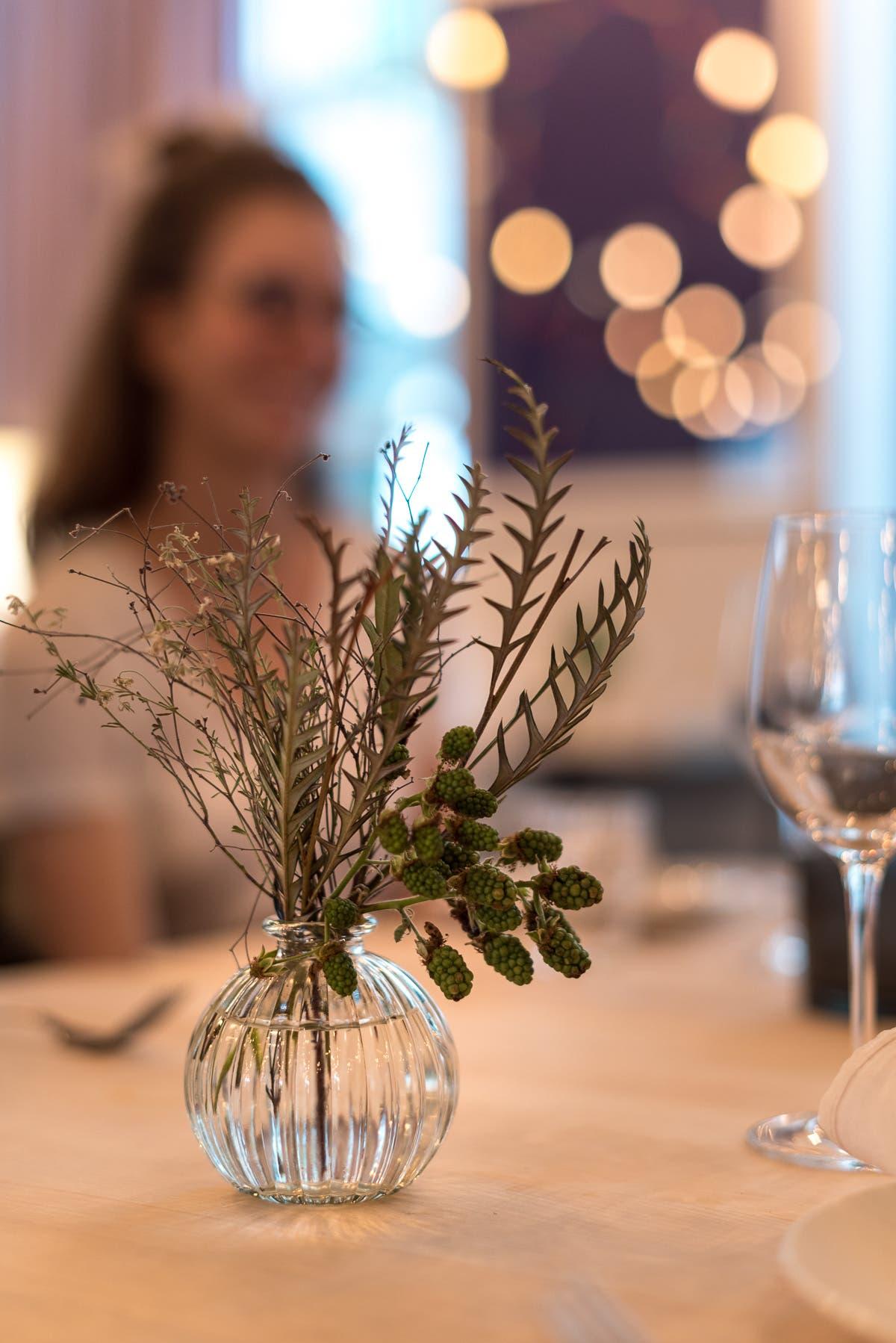 Tischdekoration mit einer Vase und grünen Zweigen und einem Weinglas.