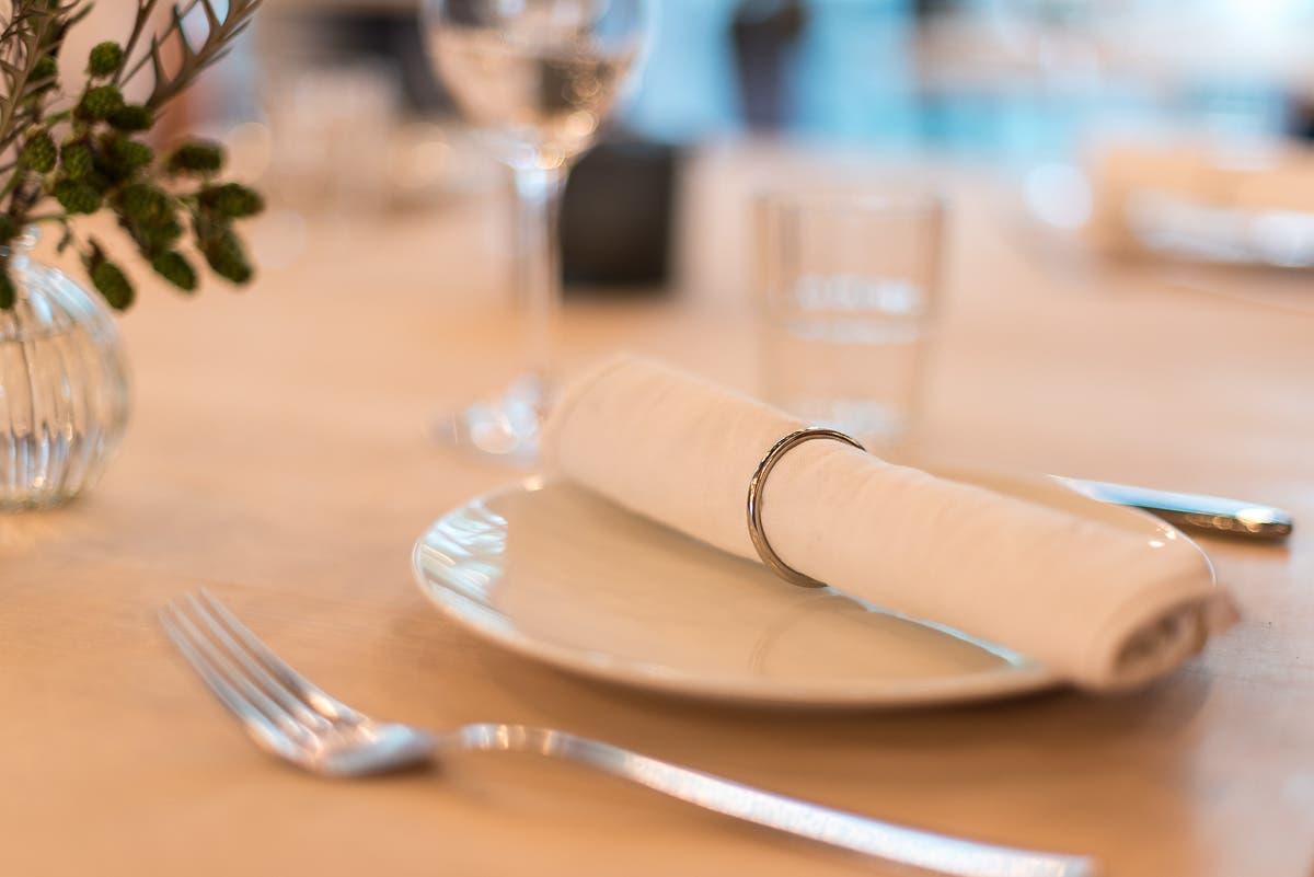 Ein Tisch mit weißem Teller, einer Serviette und Besteck.