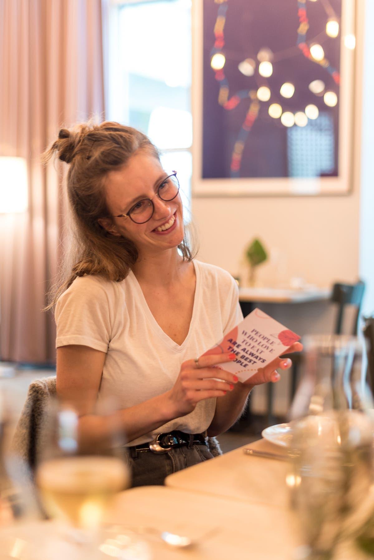 Frau sitzt an einem Tisch und lächelt und hält eine Postkarte in der Hand.