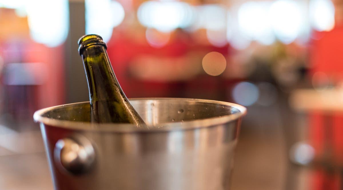 Eine Weinflasche in einem silbernem Eimer.