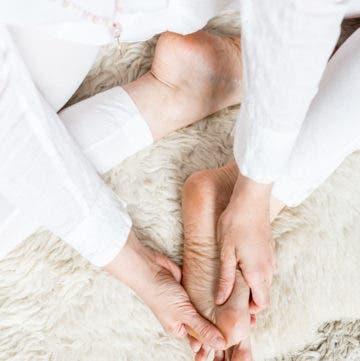 Person sitzt auf Fell und massiert sich den Fuß