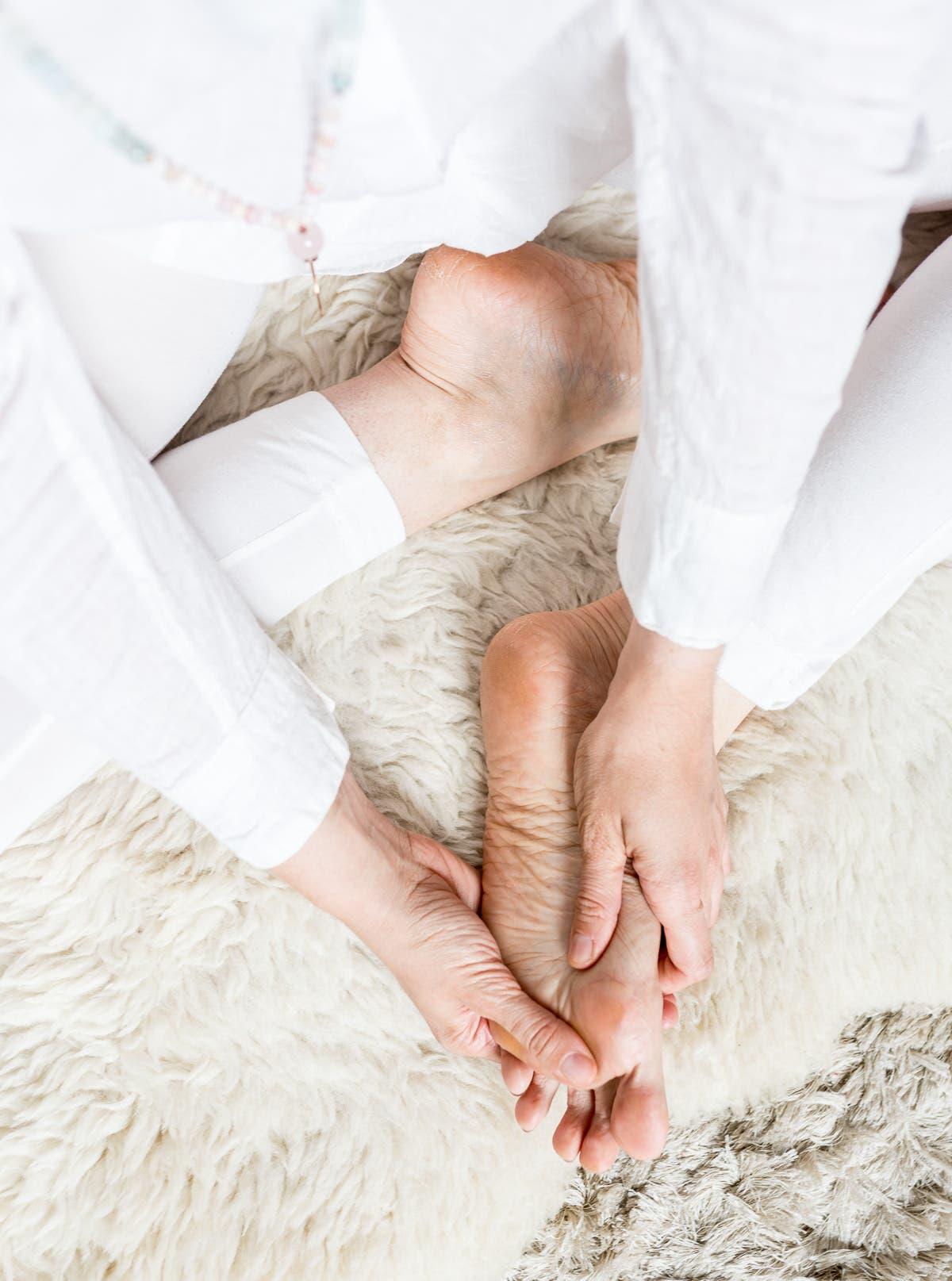 Topshot von einer Person in weißer Kleidung, die ihre Füße selbst massiert.