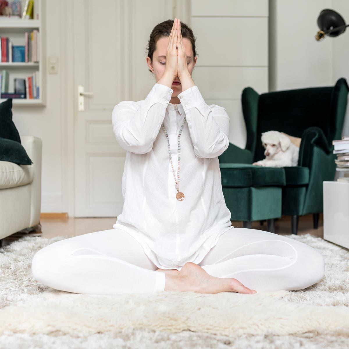 Frau sitzt im Schneidersitz meditierend auf einem weißen Teppich.
