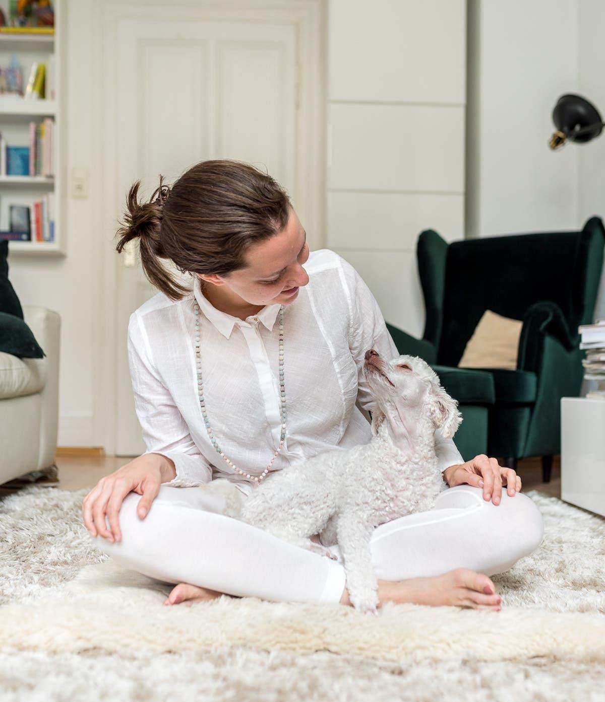 Frau sitzt auf einem Teppich und lächelt einen Pudel an.