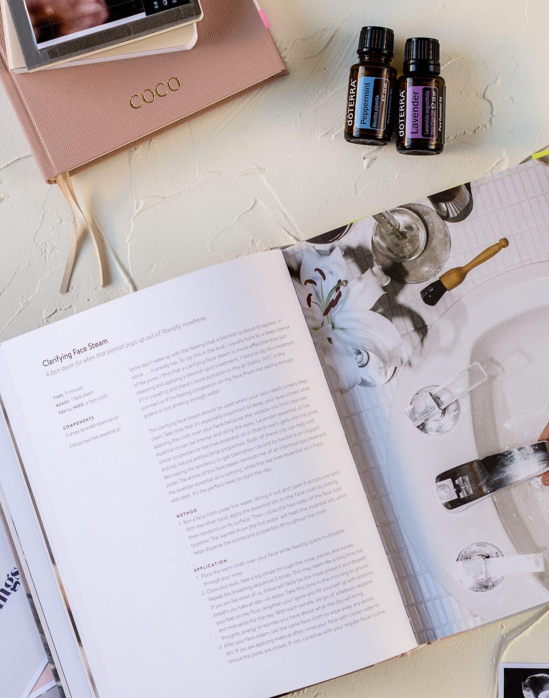 Aufgeschlagenes Buch über selbstgemachte Kosmetik und zwei ätherische Öle in kleinen dunklen Flaschen.