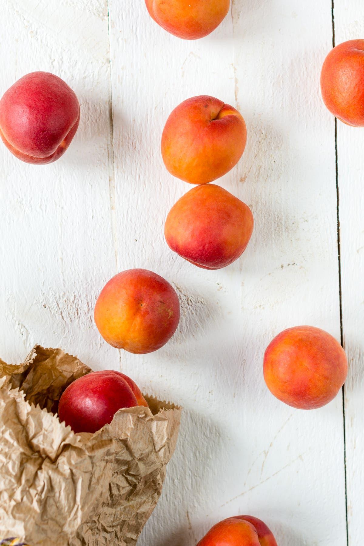 Frische Aprikosen auf einem weißem Untergrund und eine braune Papiertüte mit Aprikosen drin.