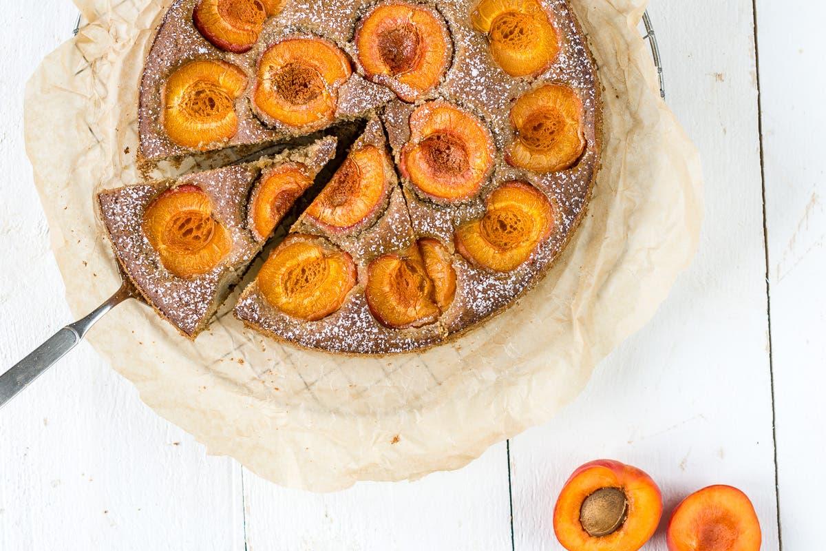 Bild von oben von einem Aprikosenkuchen mit einer Kuchengabel auf weißem Untergrund. und Backpapier