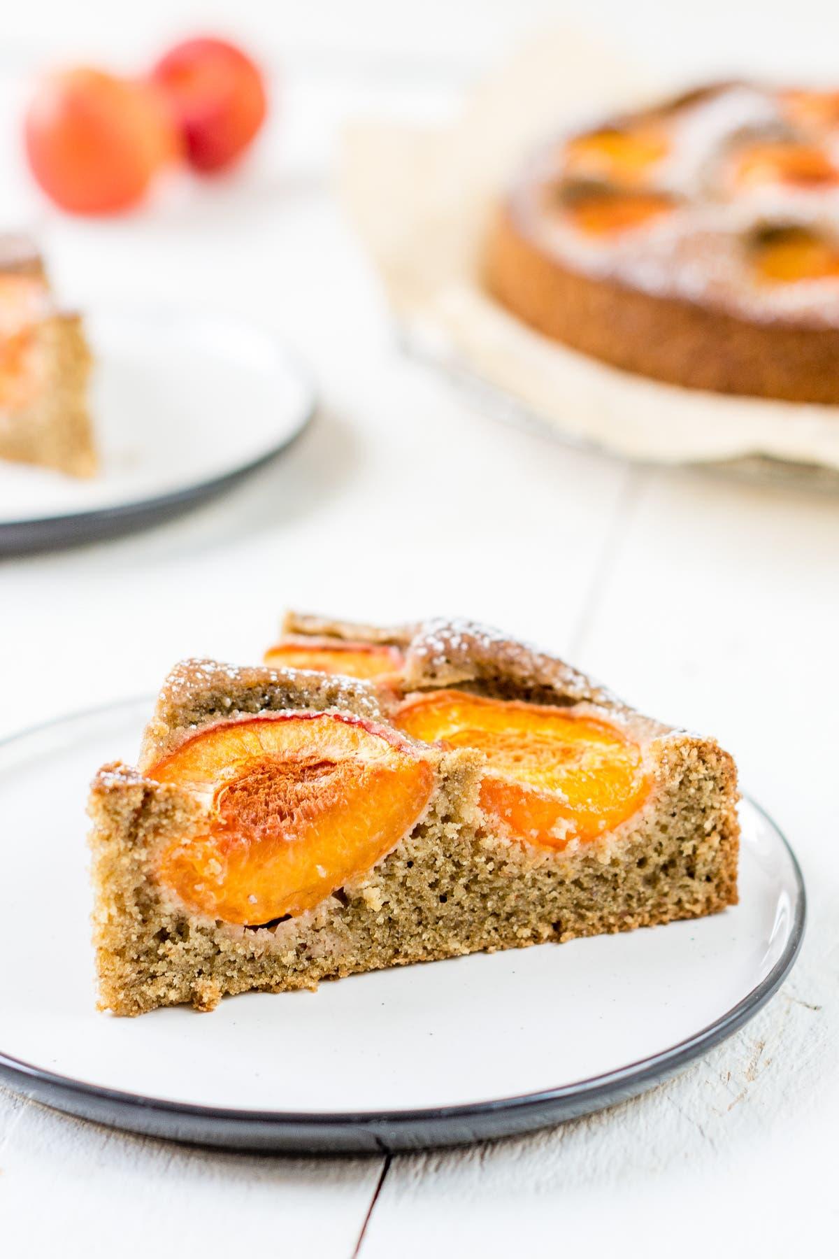 Ein Stück Aprikosenkuchen auf einem weißem Teller.