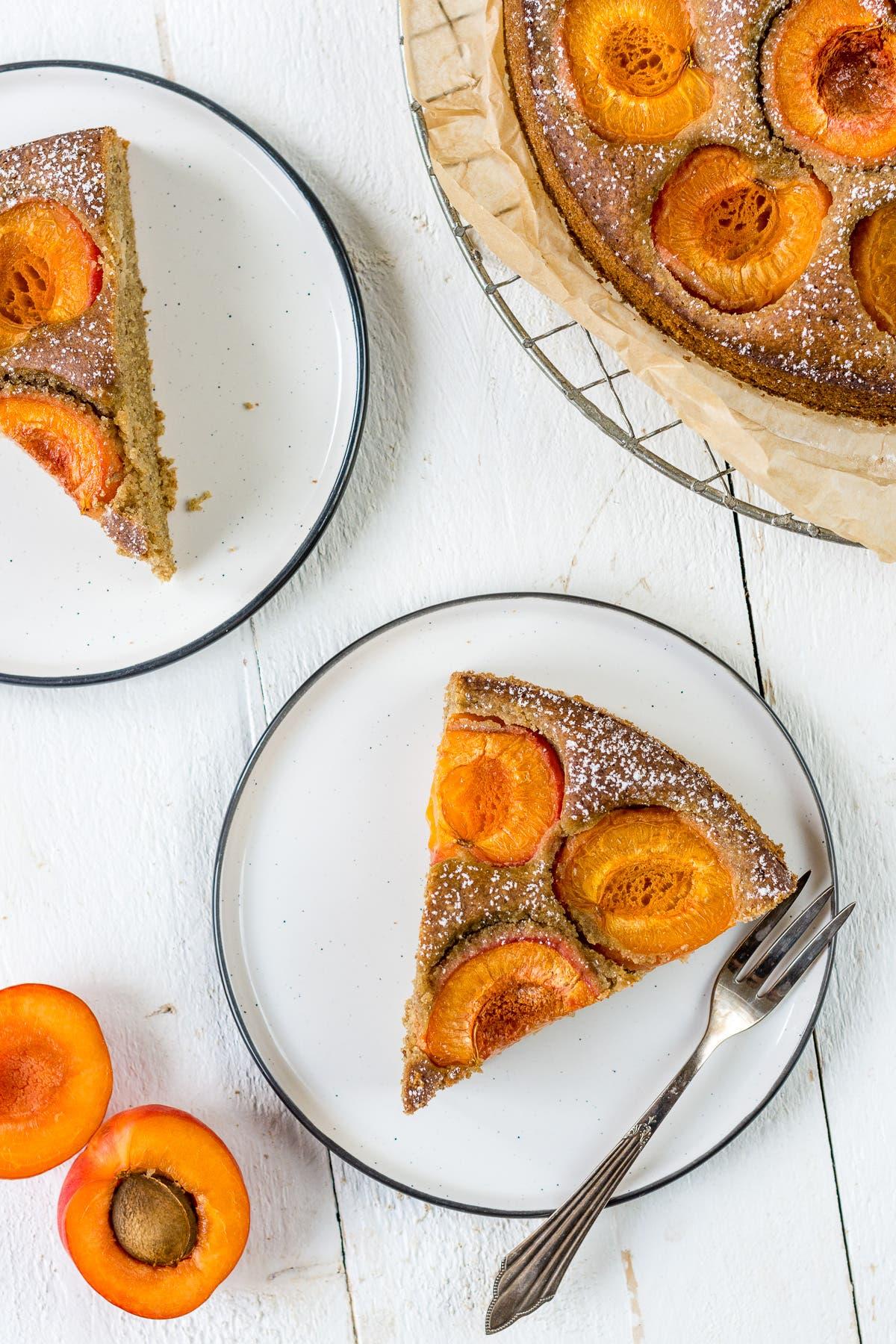 Zwei Stück Aprikosenkuchen auf weißen Tellern mit einer Gabel und frische Aprikosen.