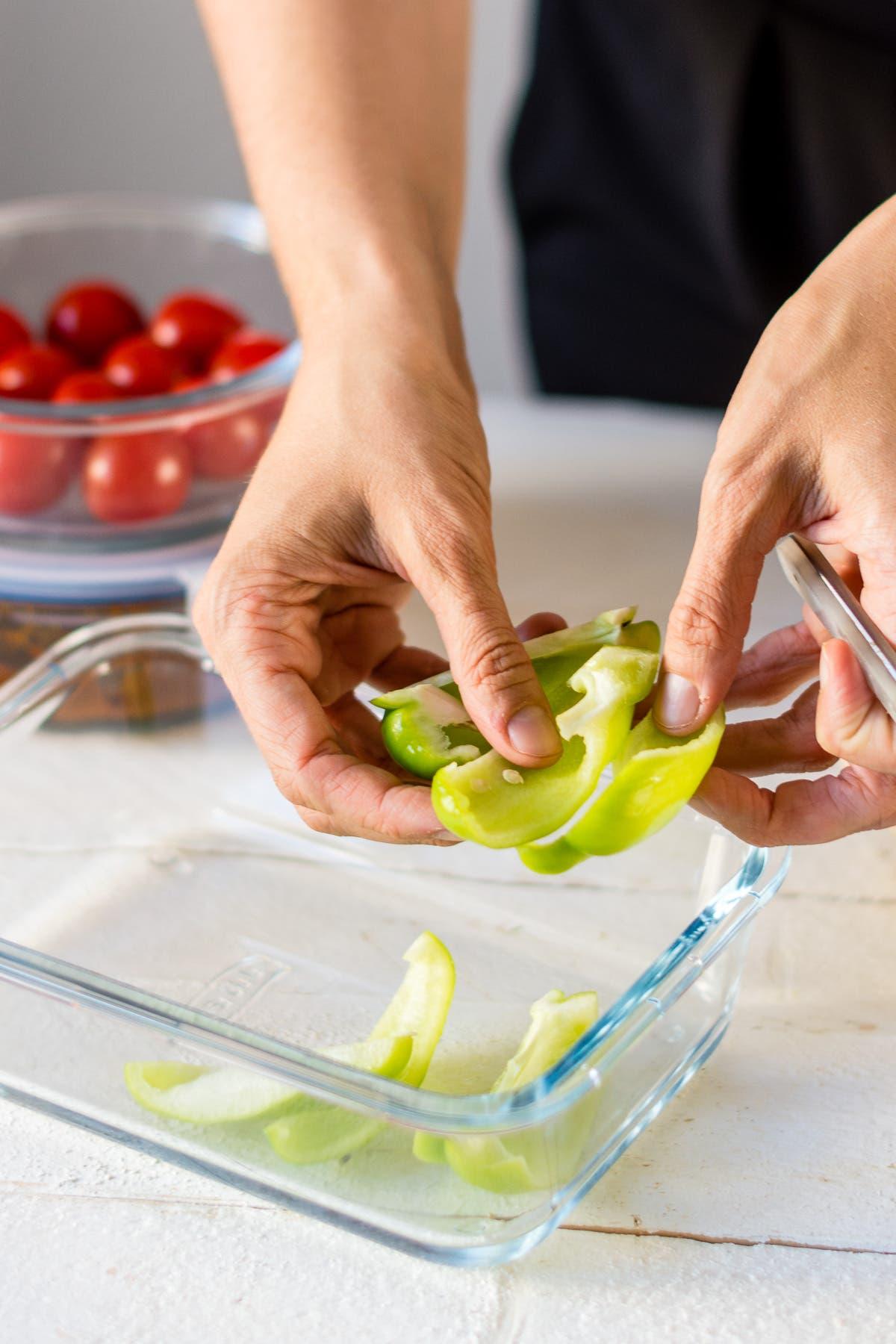Hände, die grüne Paprika vorschneiden, um beim Kochen Zeit zu sparen