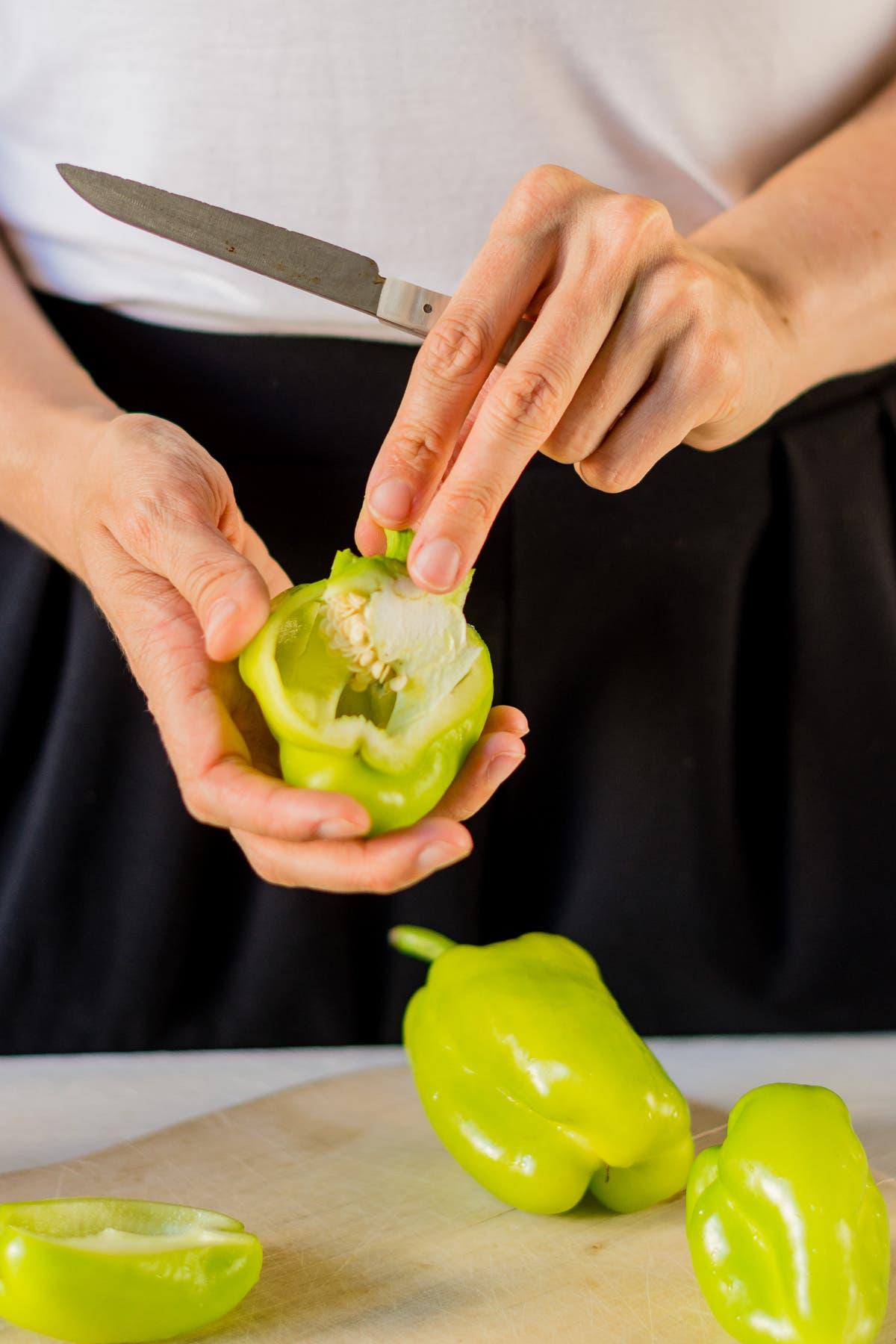 Hände mit Messer, die Paprika vorschneiden, um beim Kochen Zeit zu sparen