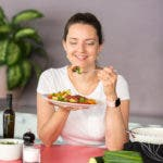 Frau mit Teller in der Hand schaut auf eine Gabel mit Gemüse.