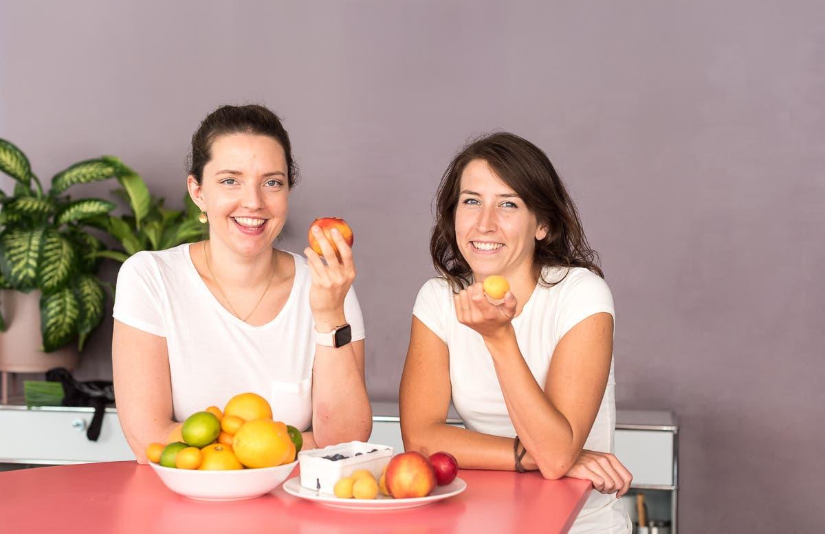 Zwei Frauen mit Obst in der Hand schauen lachend in die Kamera.