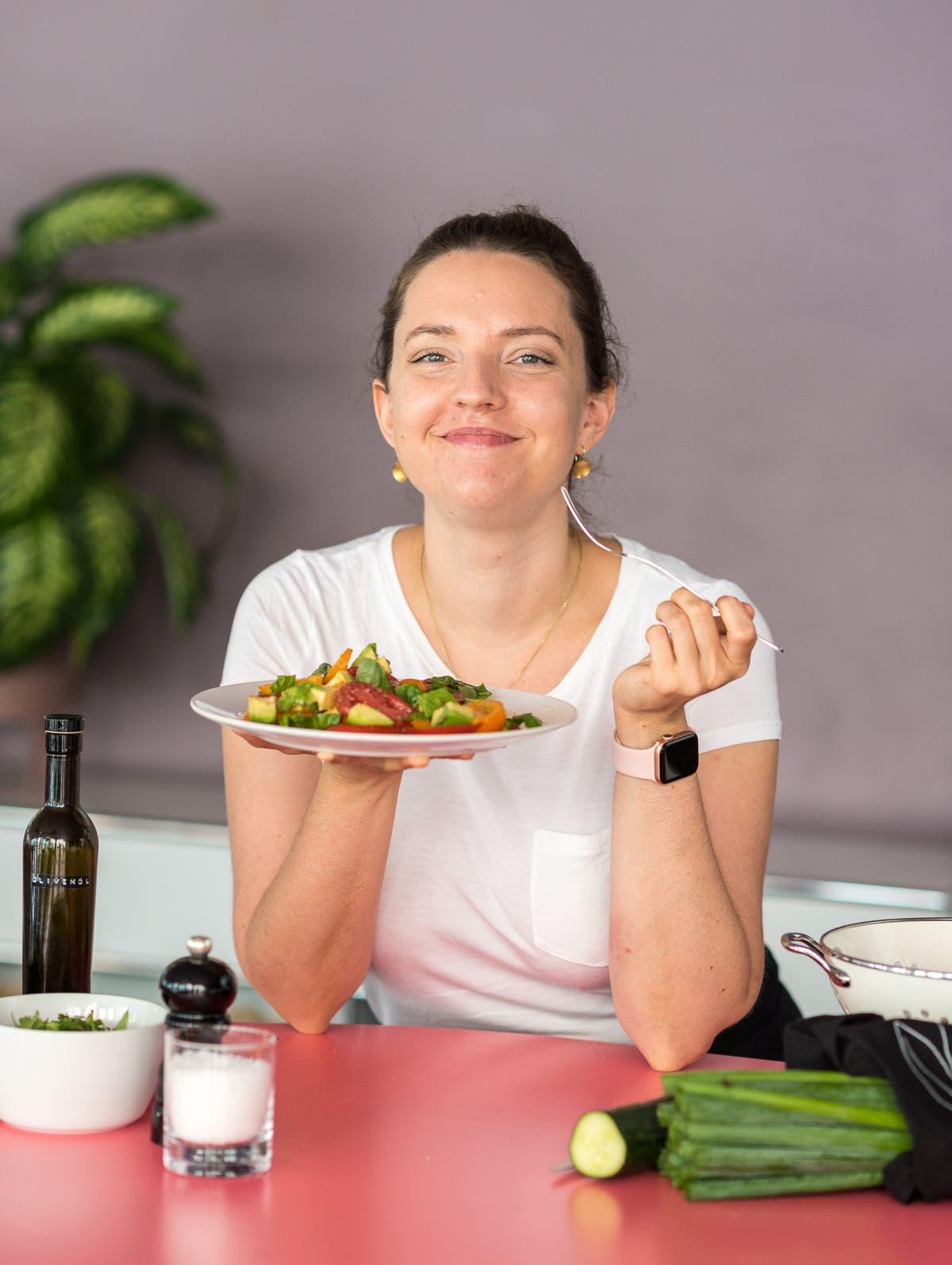 Frau hält Teller und Gabel in ihren Händen und lächelt in die Kamera