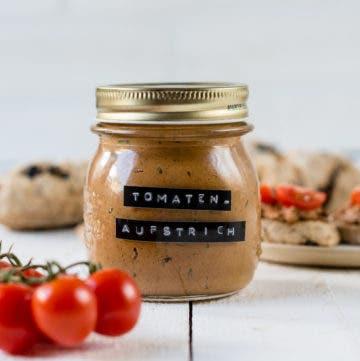 Glas mit Tomatenaufstrich. Belegtes Brot und frische Tomaten.