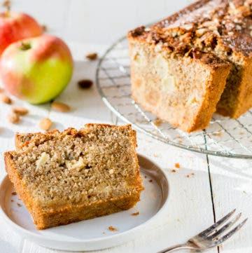 Aufgeschnittener Apfelkuchen auf einem Gitterrost und ein Stück Apfelkuchen auf einem weißem Teller.