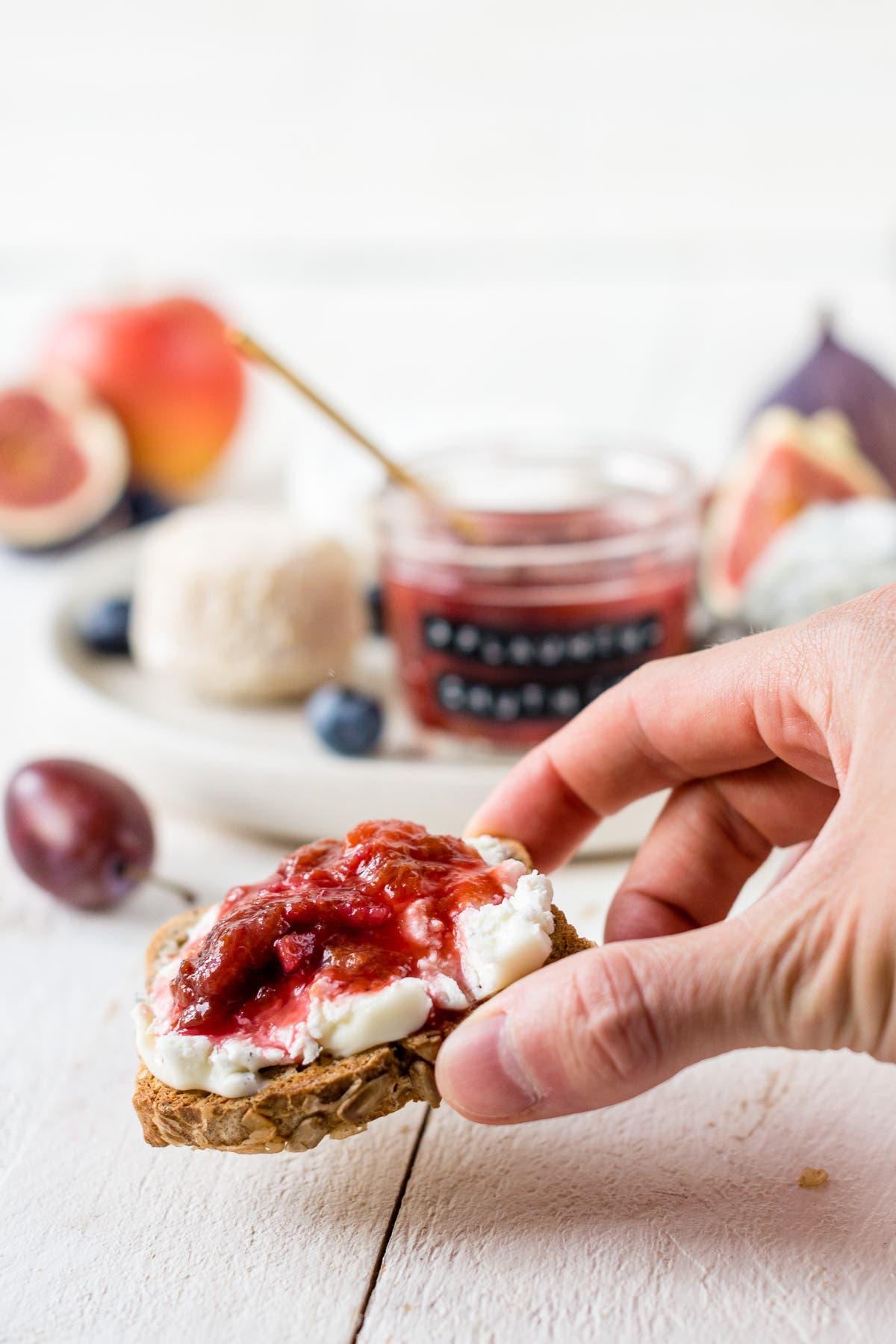 Hand hält ein Stück Brot mit Käse und Zwetschgen Chutney in der Hand.