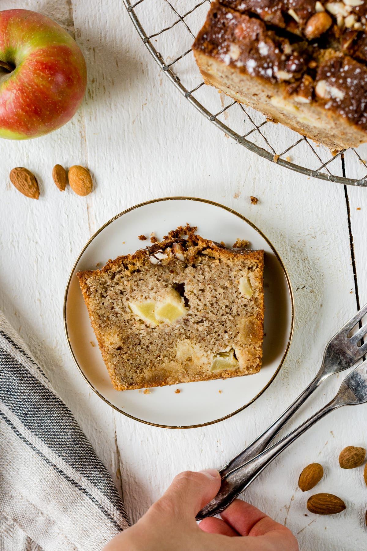Topshot von einem Stück Apfelkuchen auf einem weißem Teller und ein angeschnittener Apfelkuchen auf einem Gitterrost.
