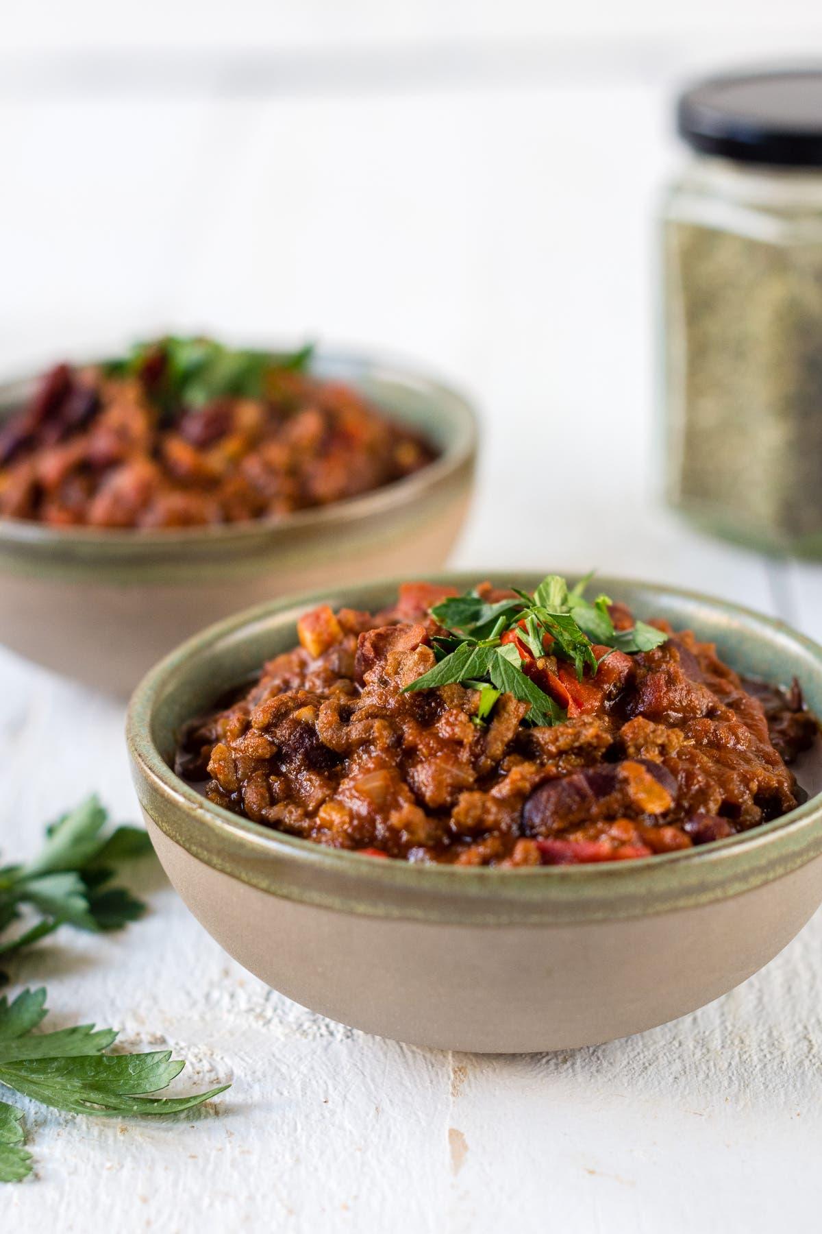 Zwei Schüsseln Chili von Carne mit Kräutern.