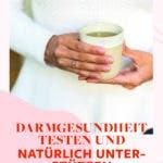 Person mit weißem Pullover hält eine Tasse Tee vor dem Bauch.