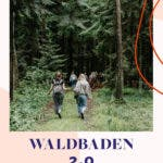 Zwei Frauen laufen einen Waldweg mit Nadelbäumen entlang.