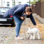 Frau beugt sich zu ihrem weißem Pudel und streichelt ihn auf der Straße.