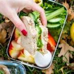 Hand hält ein belegtes Brot für unterwegs über einer Edelstahldose mit Gemüse und Obst fest.